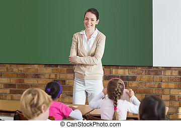 Cute pupils listening to their teacher in classroom