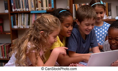 Cute pupils looking at laptop in the library in slow motion