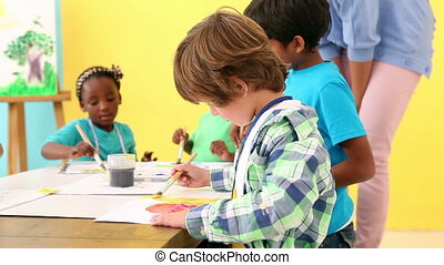 Cute pupils painting pictures with teacher at the elementary...
