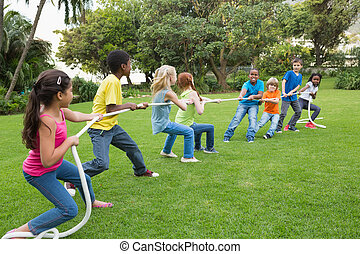 Cute pupils playing tug of war on the grass outside at the...