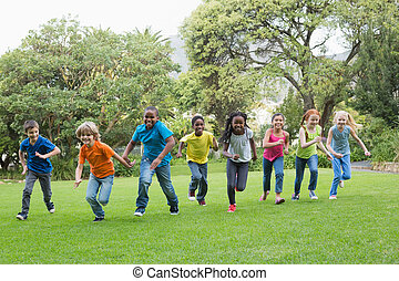Cute pupils racing on the grass outside at the elementary...