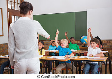 Cute pupils raising their hands in class at the elementary...