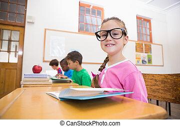Cute pupils reading at desks