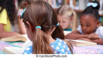 Cute pupils reading books at desk