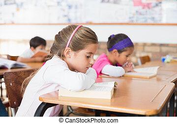 Cute pupils reading books