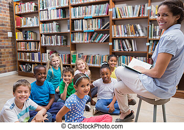 Cute pupils sitting on floor in library at the elementary...