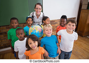 Cute pupils smiling around a globe in classroom with teacher...