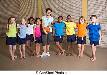 Cute pupils smiling at camera with PE teacher at the...