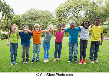 Cute pupils standing on the grass outside at the elementary school