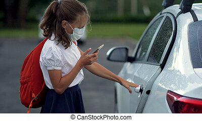 Cute pupils using smartphones at the elementary school. Boy and girl in safety masks with gadgets in their hands.