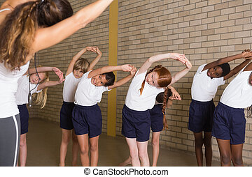 Cute pupils warming up in PE uniform at the elementary...