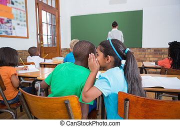 Cute pupils whispering in classroom at the elementary school