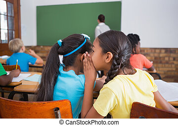 Cute pupils whispering in classroom
