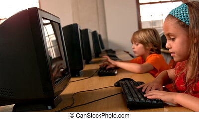 Cute pupils working on computers