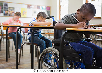 Cute pupils writing at desks in classroom at the elementary...