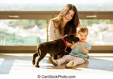 Cute puppy kissing a little girl