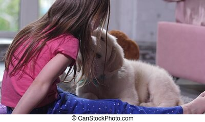 Cute puppy sniffing little child sitting on floor - Close-up...
