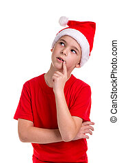 Cute puzzled looking boy, santa hat on his head, with the finger near the lips. Concept: christmas or Happy New Year holiday