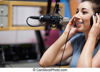 Cute radio host speaking through a microphone