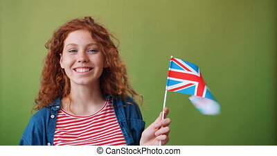 Cute red-haired girl holding British flag on green...