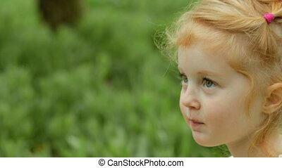 Cute red-haired girl in dress sitting on the blanket on the picnic in the garden in slow motion