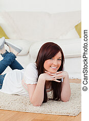 Cute red-haired woman posing while lying on a carpet