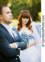 cute redhead bride holding bouquet and looking at groom