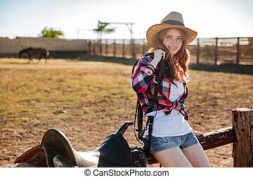 Cute redhead cowgirl sitting and resting on the ranch fence...