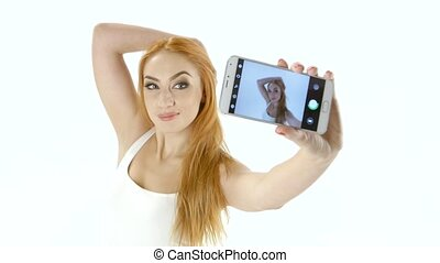 Cute redhead girl doing selfie on your smartphone. White background