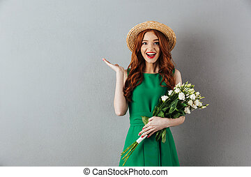 Cute redhead young woman holding flowers.