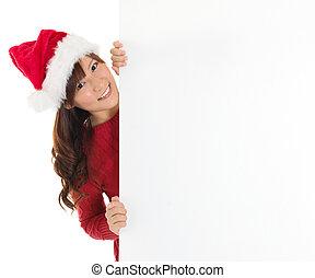 Cute Santa girl peeking from behind blank sign