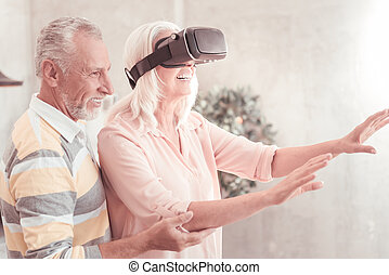 Cute satisfied woman using the VR glasses and smiling.