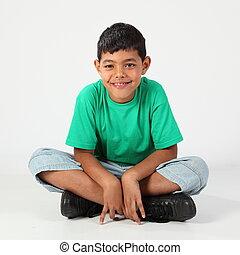 Cute school boy cross legged - Smiling school boy sitting...
