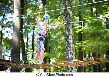 Cute school boy enjoying a sunny day in a climbing activity...