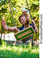 Cute school boy enjoying a swing ride