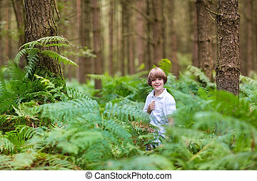 Cute school boy playing in a beautiful pine forest