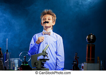 Cute school boy posing with fake mustache in lab