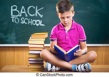 Cute school boy reading book in classroom