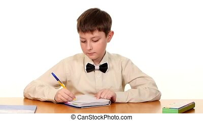 Cute school boy sitting, thinking and writing homework in workbook on white background, slow motion