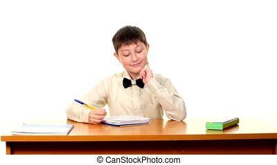 Cute school boy sitting, thinking and writing homework in workbook on white background