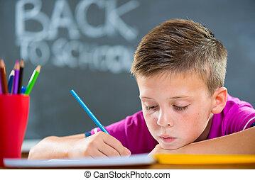 Cute school boy studying in classroom