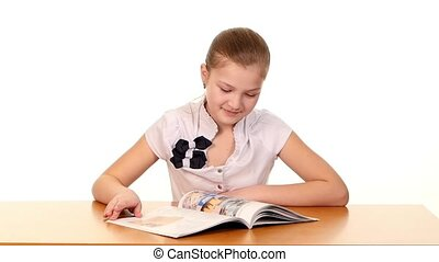 Cute school girl sitting, thinking and writing homework, essay in workbook on white background, slow motion