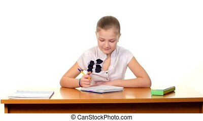 Cute school girl sitting, thinking and writing homework, essay in workbook on white background