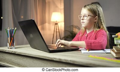 Cute school girl typing on laptop at home