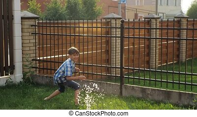 cute short haired schoolboy in checkered shirt enjoys drops flowing from water gun on sunny day close view slow motion