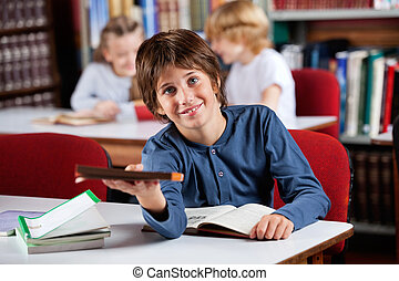Cute Schoolboy Giving Book While Sitting At Table In Library