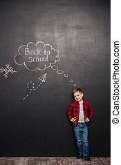 Cute schoolboy standing over background of chalkboard with school drawings
