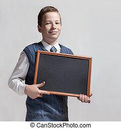 Cute schoolboy with empty chalkboard