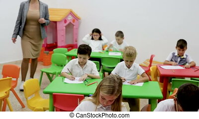 Group of schoolkids drawing in circle with their cheerful female teacher