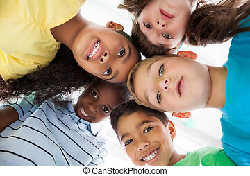 Cute schoolchildren smiling at camera from above